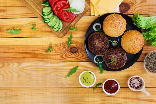 Ingredientes para hambúrguer em madeira. vista do topo