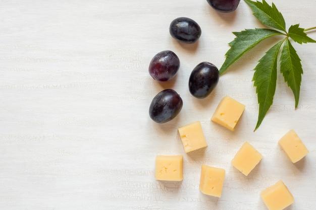 Ingredientes para lanches, queijo com azeitonas em uma mesa branca