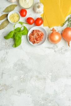Ingredientes para lasanha em fundo cinza com espaço de cópia