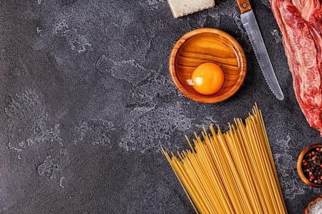 Ingredientes para macarrão carbonara em mesa de cimento