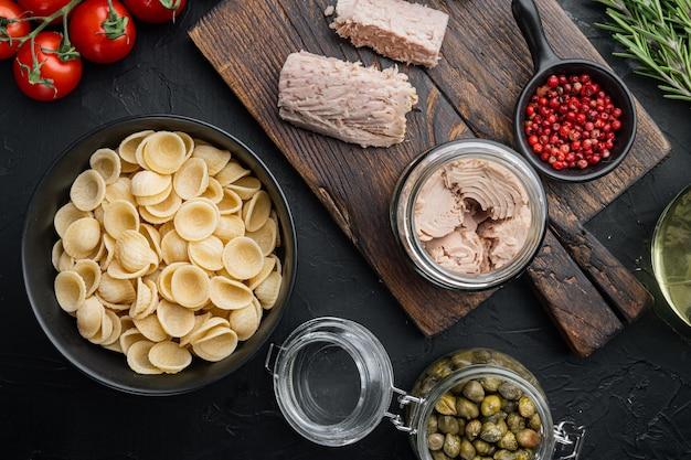 Ingredientes para macarrão de atum de sêmola de trigo duro na vista superior preta