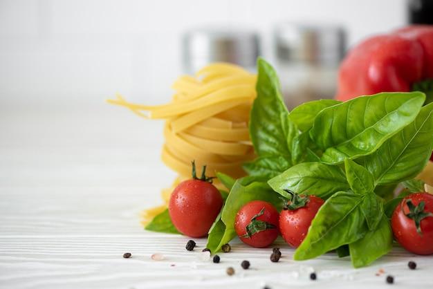Ingredientes para macarrão fettuccine com tomate, especiarias e manjericão