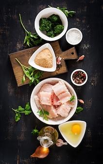 Ingredientes para o bacalhau caseiro do bolo de peixes, o espinafre, o ovo e a farinha de rosca.