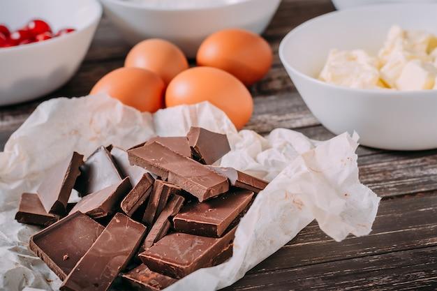 Ingredientes para o chocolate brauni com cerejas em fundo de madeira