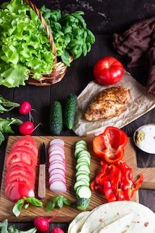 Ingredientes para o envoltório: tortilhas de farinha de trigo, frango assado, vários legumes, salada verde e manjericão com molho na placa de madeira.