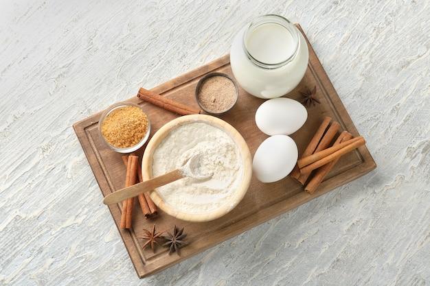 Ingredientes para pãezinhos de canela na placa de madeira