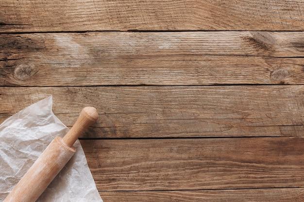 Ingredientes para panificação e utensílios de cozinha em fundo de madeira velho. cozinhar massa de pão, preparar farinha, pino de balanço, papel manteiga. foto plana do conceito de cozimento com espaço de cópia
