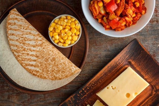 Ingredientes para quesadilla, burito, taco, sobre uma mesa de madeira