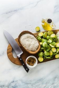 Ingredientes para risoto com couve de bruxelas sobre uma tábua de madeira e mesa de mármore