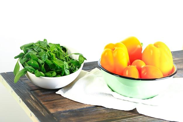 Ingredientes para salada de legumes de verão. espinafre fresco e pimentão em uma mesa de madeira