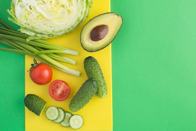 Ingredientes para salada em uma tábua amarela