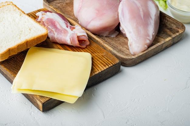 Ingredientes para sanduíche, bacon, queijo, tomate, carne de frango, alface, molho, em fundo branco com espaço de cópia para o texto