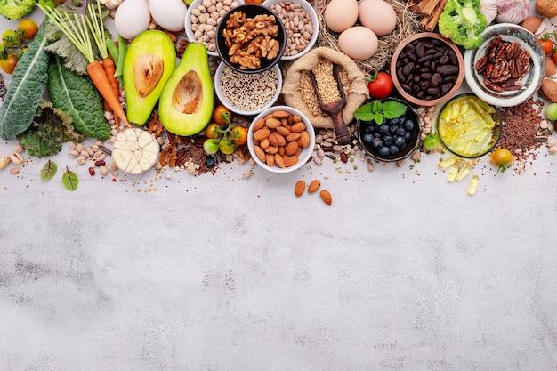 Ingredientes para seleção de alimentos saudáveis configurados em fundo branco de concreto.