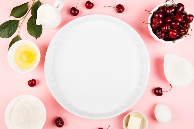 Ingredientes para torta de cereja - leite, manteiga, ovos, farinha, cereja, açúcar em um fundo rosa