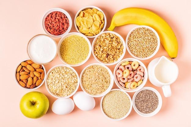 Ingredientes para um café da manhã saudável - cereais, grãos, laticínios, sementes, nozes e frutas.