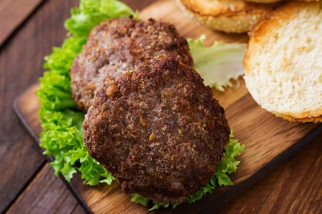 Ingredientes para um sanduíche - hambúrguer de hambúrguer com carne, picles, tomate e cebola vermelha em fundo de madeira.