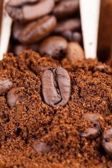 Ingredientes que podem ser usados para fazer uma bebida de café quente e revigorante, pó de feijão e grãos de café inteiros, grãos de café torrados são colocados no café moído