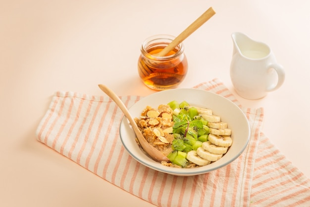 Ingredientes saborosos café da manhã saudável para cozinhar com leite e flocos de aveia, banana, kiwi em fundo rosa