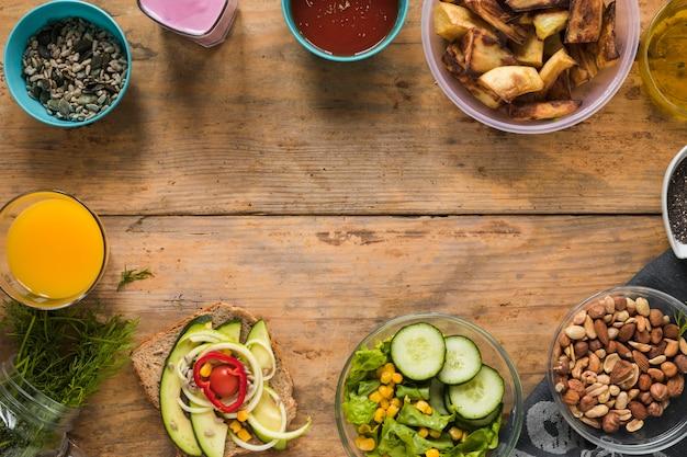 Ingredientes; suco; frutas secas; batata torrada; smoothie; sanduíche e óleo dispostos na mesa de madeira