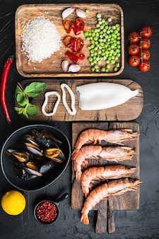 Ingredientes tradicionais da paella valenciana de frutos do mar com camarões, mexilhões, arroz e temperos no preto