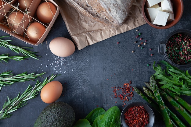 Ingridients para cozinhar. legumes frescos e orgânicos, pão sem glúten, ovos ecológicos e salsa. legumes da primavera, abacate no fundo escuro de pedra, com espaço de cópia. postura plana. conceito de comida saudável