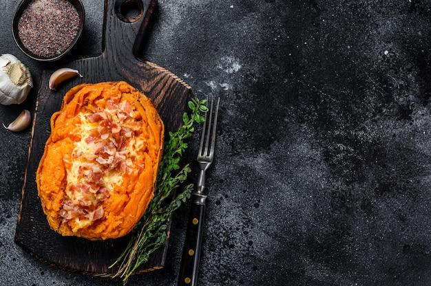 Inhame de batata-doce assado recheado com carne moída e queijo. fundo preto. vista do topo. copie o espaço.