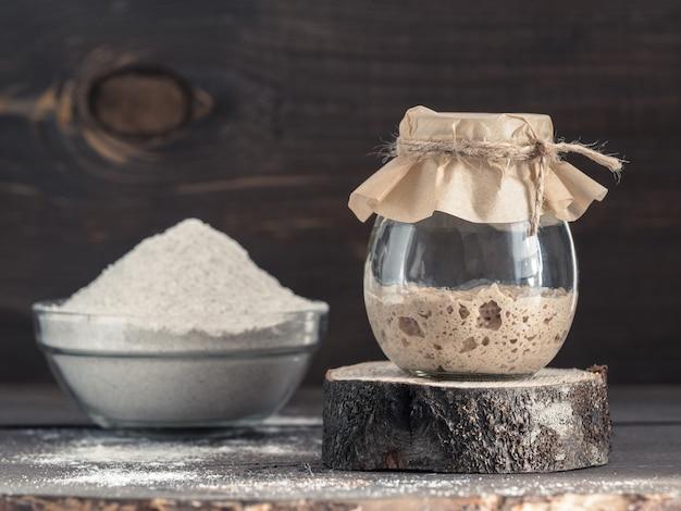 Iniciador de massa fermentada de centeio ativo em frasco de vidro e farinha de centeio em fundo de madeira marrom iniciador para pão de massa fermentada tonificado imagem cópia espaço
