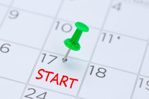 Iniciar escrito em um calendário com um pino de empurrar verde para lembrá-lo e compromisso importante.
