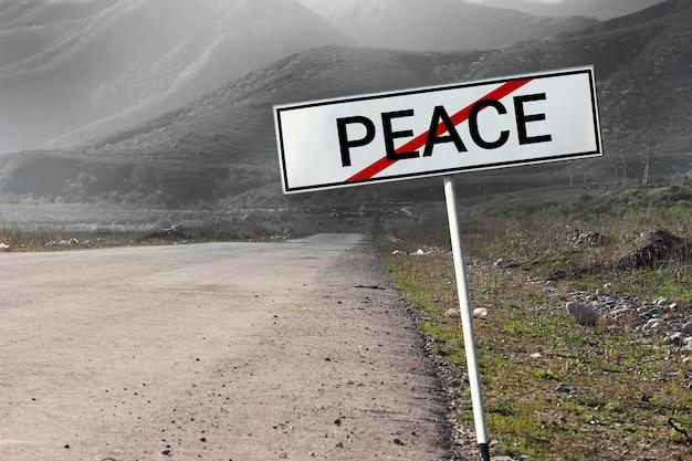 Início da guerra. a estrada e o sinal de estrada riscaram a palavra paz. conceito de guerra.