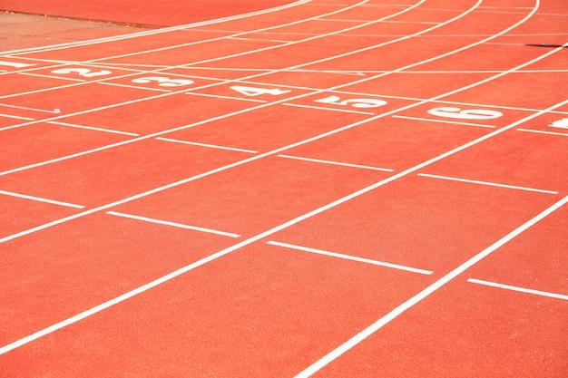 Início da pista atlética vermelha com números. conceito de esporte