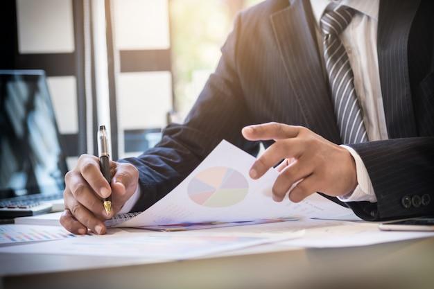 Início do processo de trabalho. empresário que trabalha na mesa de madeira com novo projeto de finanças. caderno moderno na mesa. pen segurando a mão.