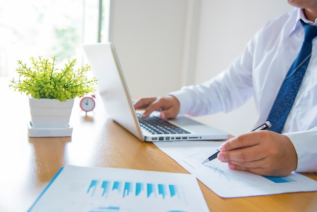 Início do processo de trabalho. empresário trabalhando na mesa de madeira com novo projeto de finanças. caderno moderno na mesa. caneta segurando a mão