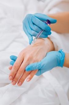 Injeção sendo feita na mão feminina durante o procedimento no salão de beleza