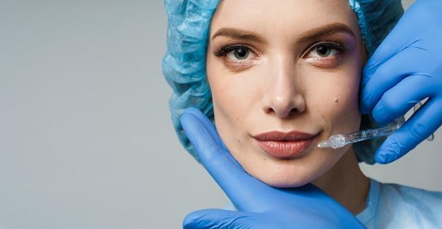 Injeções de aumento de lábios em close-up para garota atraente em superfície branca
