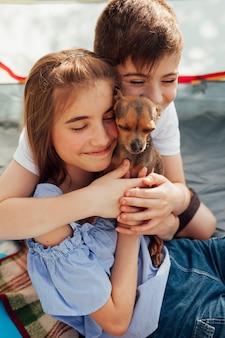 Inocente irmão sorridente amando seu animal de estimação em tenda