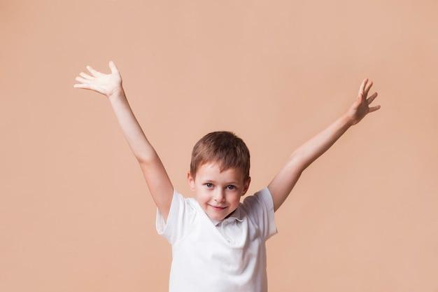 Inocente menino sorridente com a mão levantada em pé na frente de fundo bege