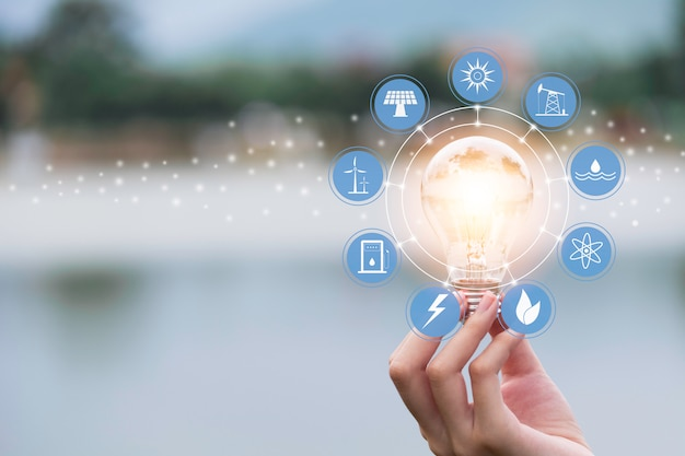 Inovação e conceito de energia da mão segura uma lâmpada
