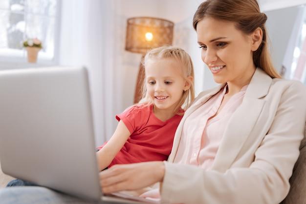 Inovações digitais. mulher feliz, positiva e simpática sorrindo e pressionando um botão enquanto mostra à filha como usar o laptop