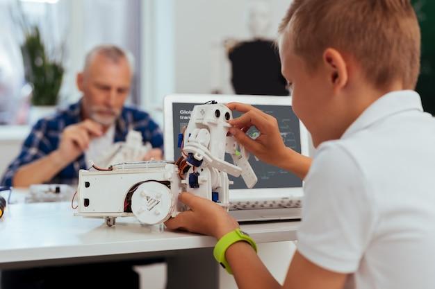 Inovações modernas. menino bonito e bonito sentado em frente ao computador enquanto brinca com um robô