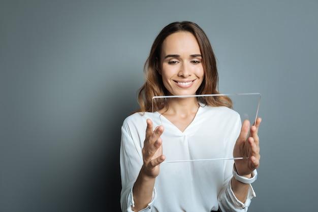 Inovações modernas. mulher bonita encantada positiva segurando um tablet e sorrindo enquanto o usa