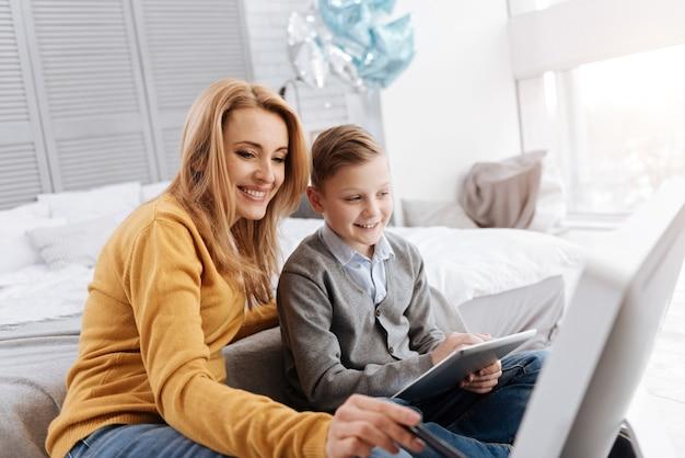 Inovações progressivas. alegre positiva e simpática mãe sorrindo e olhando para a tela digital enquanto está em casa com seu filho