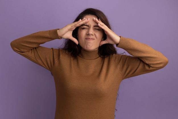 Insatisfeita com os olhos fechados, bela jovem vestindo uma blusa de gola alta marrom colocando as mãos na têmpora isolada na parede roxa