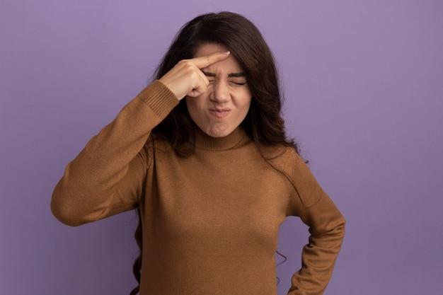 Insatisfeita com os olhos fechados, bela jovem vestindo uma blusa de gola alta marrom colocando o dedo na testa isolada na parede roxa