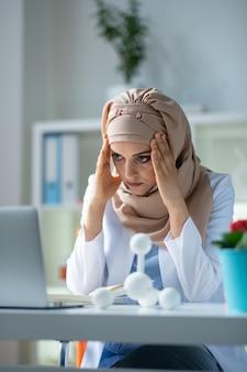 Insatisfeito após a experiência. química feminina usando lenço na cabeça e sentindo-se insatisfeita após o experimento