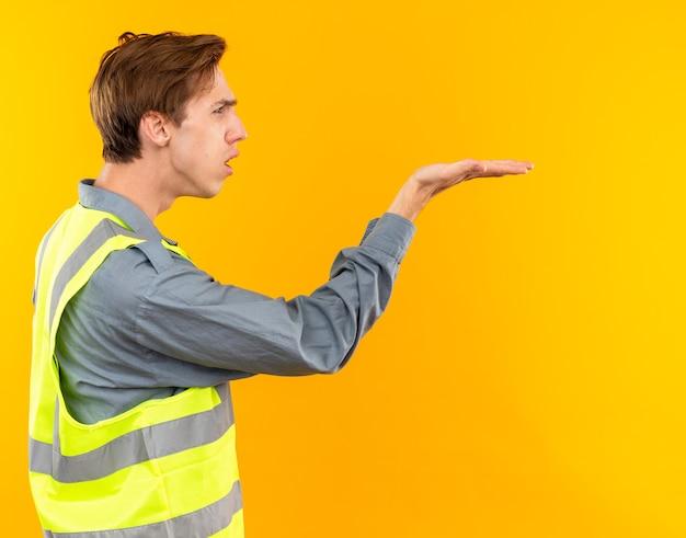 Insatisfeito de pé em vista de perfil, jovem construtor de uniforme com a mão estendida ao lado