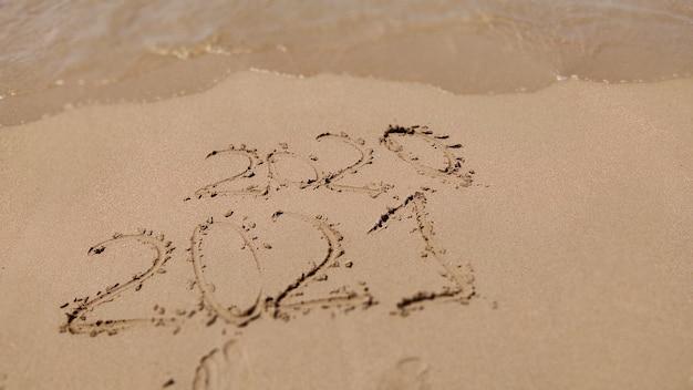 Inscrição 2020 2021 na areia da praia. conceito de ano novo