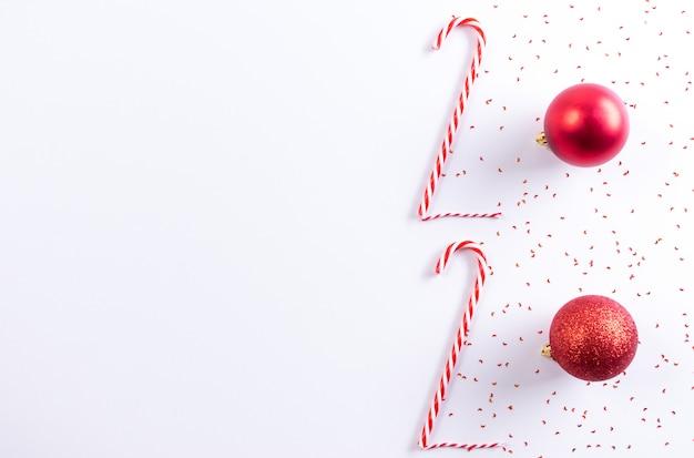 Inscrição 2020 do bastão de doces e bola vermelha em fundo branco. ano novo conceito.