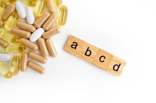 Inscrição abce em cubos de madeira em um fundo branco de diferentes pílulas