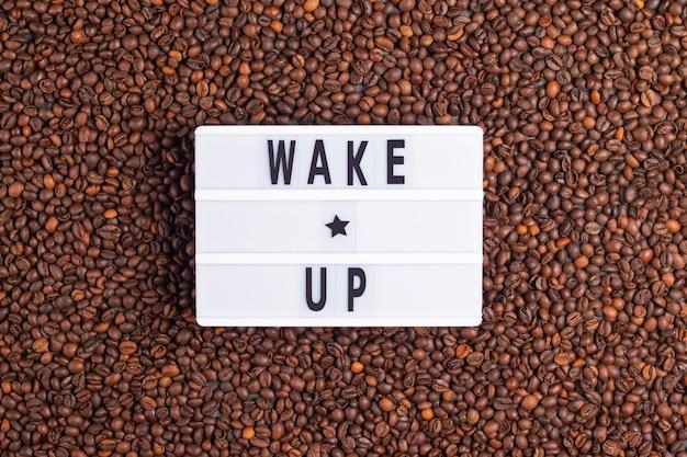 Inscrição acordar em um quadro branco sobre um fundo de café de grãos de café