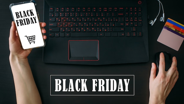 Inscrição black friday. conceito de compras online. mão segurando o smartphone com o aplicativo e usando o computador portátil.